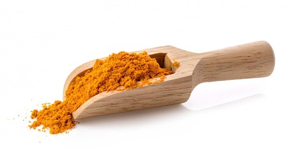 Turmeric powder in wood scoop on white wall