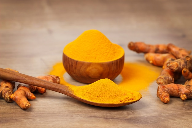 Turmeric powder in wooden bowl  and fresh turmeric on old wooden table. indian spices