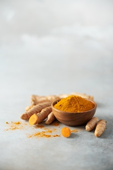 Turmeric powder in wooden bowl and fresh turmeric root on grey concrete background.