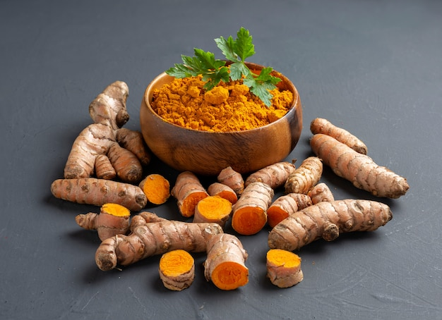 Turmeric powder in a wooden bowl and fresh turmeric