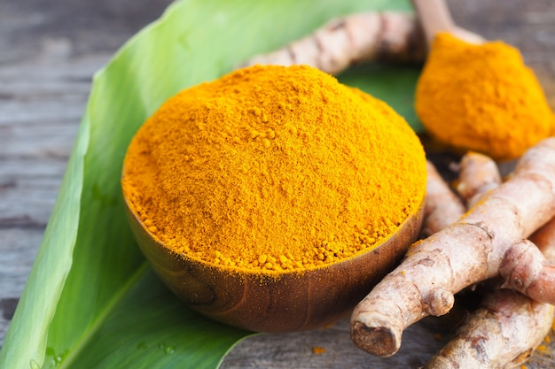Turmeric powder in wooden bowls on old wooden table. herbs