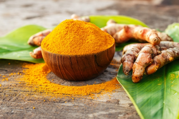 Turmeric powder in wooden bowls on wooden table