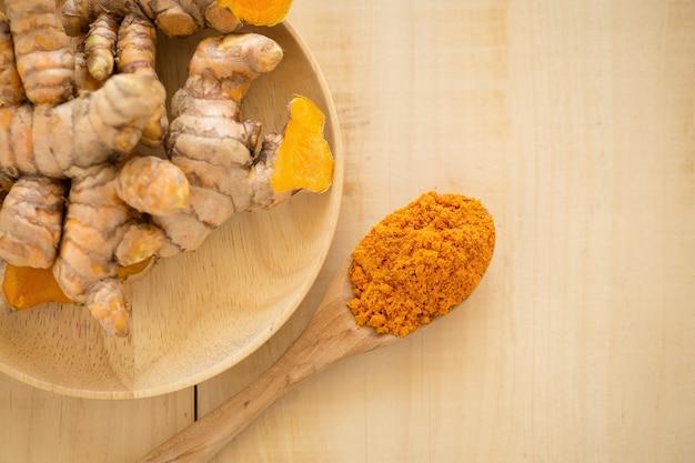 Turmeric powder in a wooden spoon and fresh turmeric