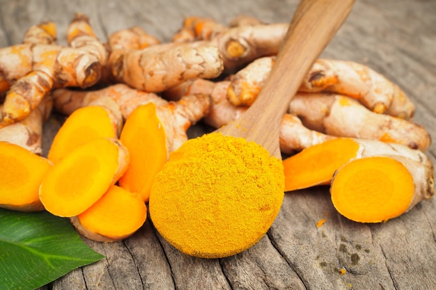 Turmeric powder in wooden spoon on old wood table
