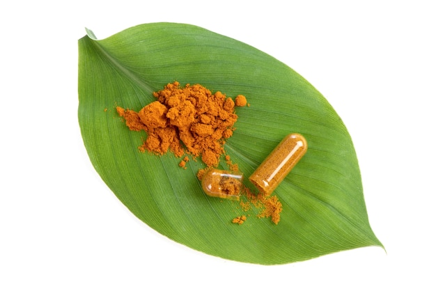 Turmeric rhizome and powder in capsule on green leaf background.top view,flat lay.