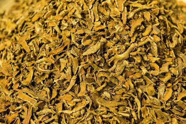 Turmeric rhizomes dried slices on nature background.