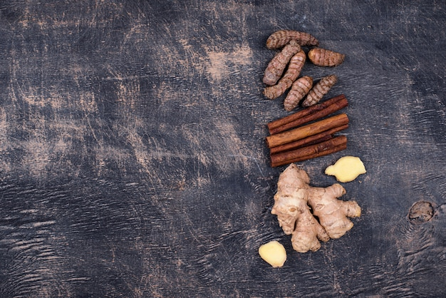 Turmeric roots, cinnamon and ginger background