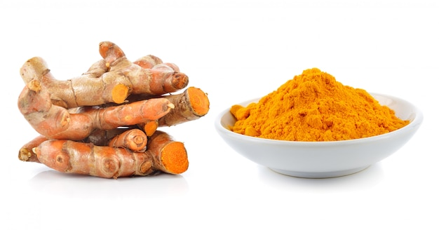 Turmeric roots with turmeric powder isolated on white