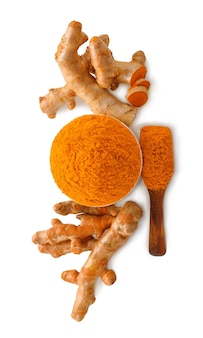Turmeric roots with turmeric powder on white