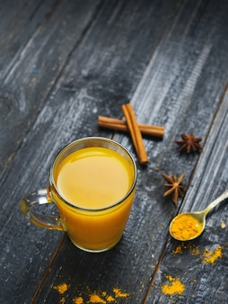 Turmeric tea in a cup of cinnamon on a wooden dark background