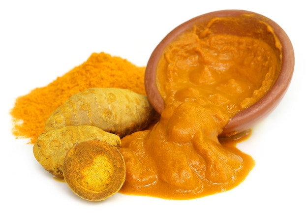 Turmeric with powder and paste on a brown bowl
