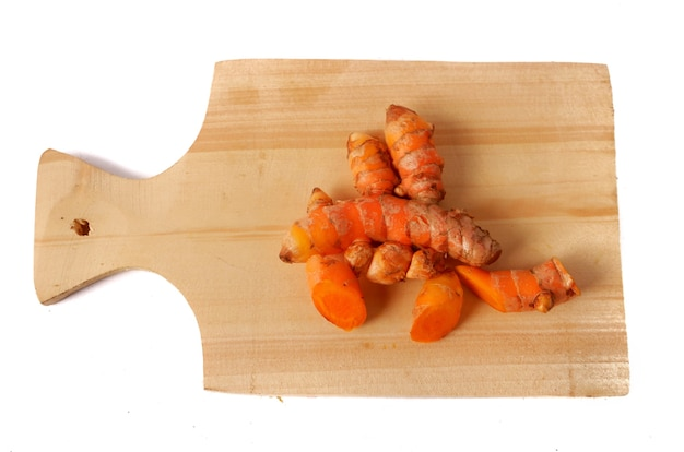 Turmeric on a wooden cutting board isolated on a white background