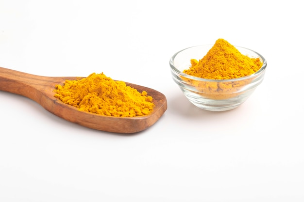 Turmeric in wooden spoon on white surface