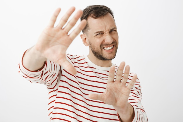 Turn off light it is to shiny. displeased uncomfortable handsome adult man in striped outfit pulling hands towards to protect face, grimacing from discomfort