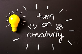Turn on creativity text written with chalk on blackboard with yellow light bulb