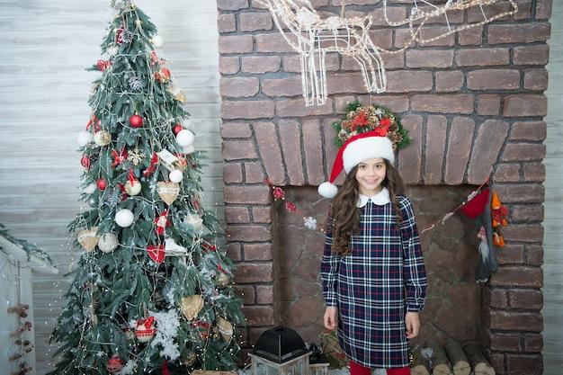 Включите гирлянду для волшебной атмосферы. концепция освещения. счастливых зимних праздников. маленькая девочка дома зажигает гирлянду. детские расслабляющие уютные гирлянды. предпосылка интерьера украшений рождественской елки.