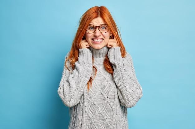 Disattiva l'audio. la giovane donna dai capelli rossi scontenta stringe i denti, tappi le orecchie per evitare rumori fastidiosi, non vuole ascoltare musica ad alto volume indossa un maglione invernale caldo.