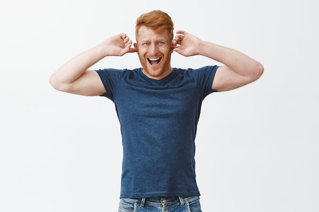 Turn this noise off. annoyed and displeased attractive ginger man with bristle in casual clothes, covering ears with index finger like earplugs, frowning and wrinkling nose from discomfort sound