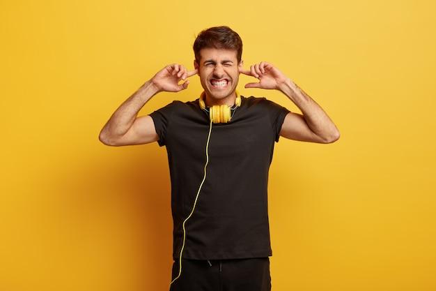 音量を上げてください!イライラした若い男は、大音量のロック音楽に不満を持って、耳を塞ぎ、歯を食いしばり、ノイズを無視します