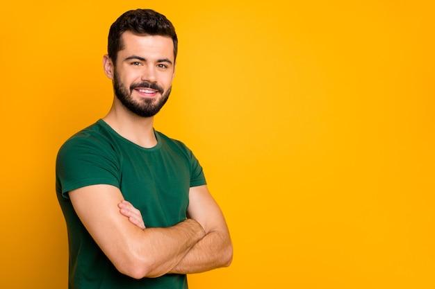 Обворожительный парень со скрещенными руками носит стильную одежду, изолированную на стене желтого цвета