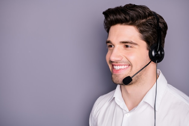 Turned close up photo of successful call center worker man wear headset listen help clients with problems isolated over grey color wall