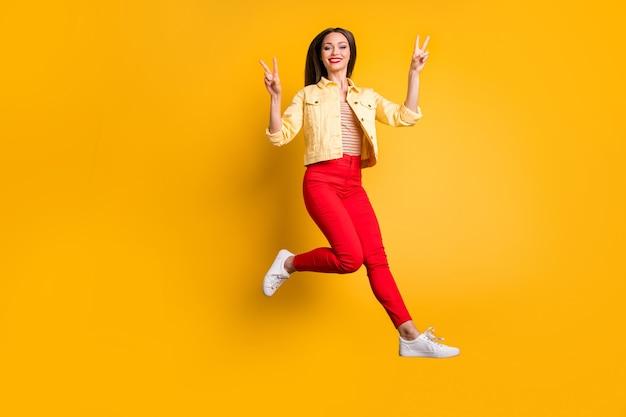 全身サイズになって元気でスタイリッシュなトレンディな白人女性が赤いズボンでダブルvサインを見せて笑う歯を見せるジャンプ孤立した鮮やかな色の壁