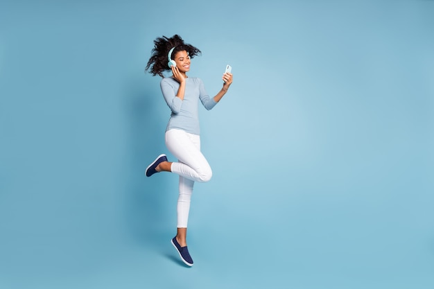 Turned full length body size photo of cheerful positive cute nice pretty girlfriend jumping up in white pants listening music isolated pastel color blue background with phone