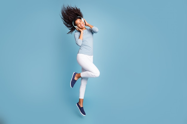 Turned full length body size photo of cheerful positive cute nice sweet girl listening to music in headphones jumping with hair flying isolated pastel blue color background