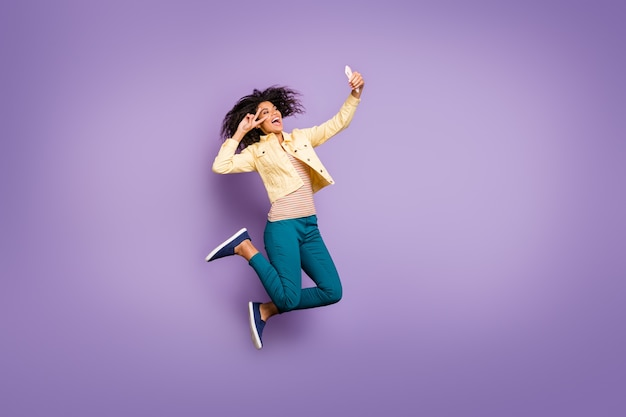 Повернутая фотография в полный рост веселой сумасшедшей возбужденной девушки в брюках брюк, показывающая, что делает селфи, прыгает, изолированные вьющиеся волнистые каштановые волосы, изолированные на пастельном фиолетовом цветном фоне