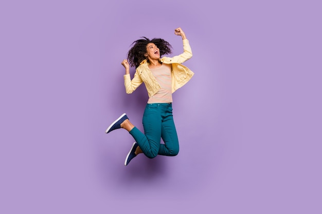 Повернутая фотография в полный рост веселой восторженной в восторге от счастья в брюках, брюках, обуви, полосатой футболке, изолированном пастельном цвете, фиолетовом фоне