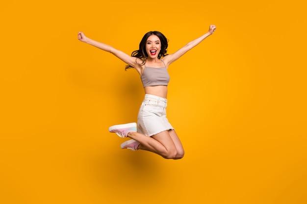 Повернутая фотография в полный рост веселой счастливой взволнованной женщины, кричащей да выигравшей приз, изолирована на ярком цветном фоне Premium Фотографии