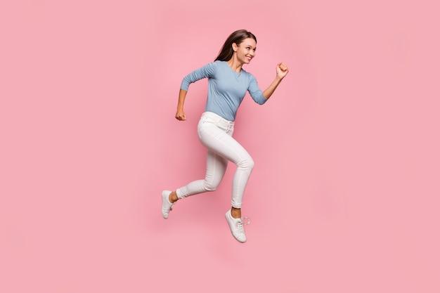 쾌활한 긍정적 인 귀여운 좋은 예쁜 여자의 전체 길이 몸 크기 사진이 흰색 신발에서 실행 점프 이빨 격리 된 파스텔 컬러 배경 웃고