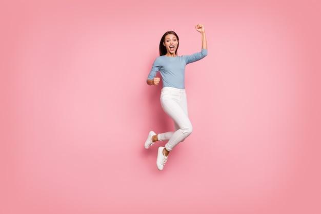 Повернутая фотография в полный рост веселой кричащей, кричащей позитивной девушки, выражающей волнение на лице, сжимающем кулак в синем свитере, изолированном пастельном цветном фоне