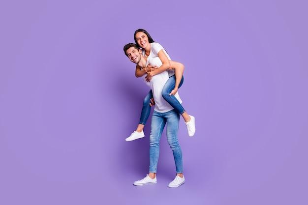 두 사랑하는 사람의 귀여운 커플의 전체 길이 몸 크기 사진이 흰색 티셔츠에 피기 백 그의 여자를 들고 남자와 이빨 미소 짓는 보라색 파스텔 컬러 배경