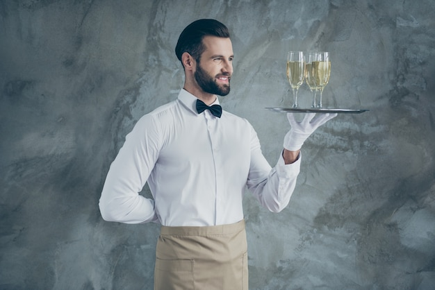 Turned photo of cheerful positive handsome waiter with hand behind his back smiling toothily holding plate with glasses of champagne isolated grey concrete wall