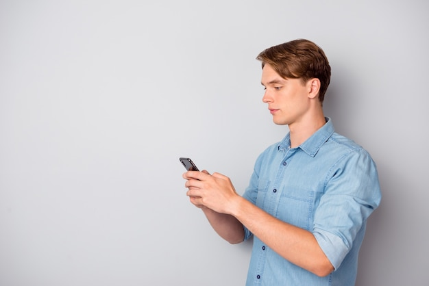 Turned photo of concentrated worker guy use smartphone chatting with colleagues clients on social media text type sms wear good looking outfit isolated over grey color background