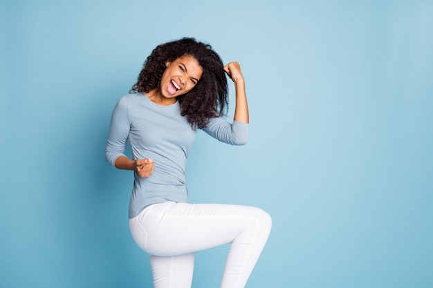 孤立したパステルカラーの青い背景に歓喜の感情を表現する白いズボンでカジュアルな失礼な大喜びの若者を叫ぶの写真を回