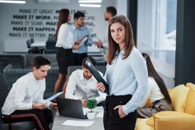 横向き。バックグラウンドで従業員とオフィスに立っている若い女の子の肖像画