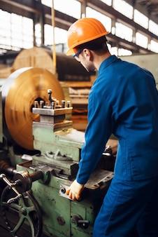 Токарь в форме и каске работает на токарном станке, заводе. промышленное производство, слесарное дело, производство силовых машин
