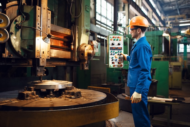 Turner in uniform and helmet works on large lathe, factory. industrial production, metalwork engineering, power machines manufacturing