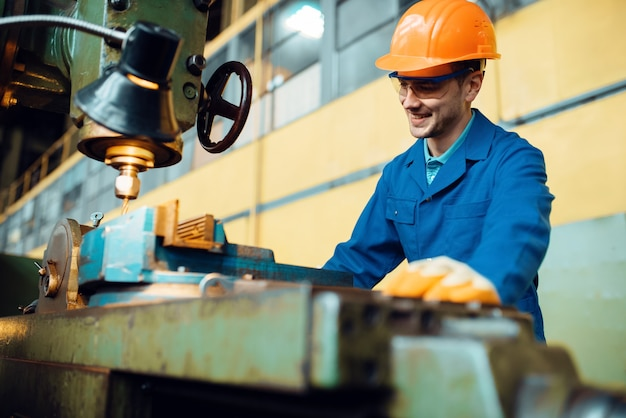 Turner in uniform and helmet works on lathe, plant. industrial production, metalwork engineering, power machines manufacturing