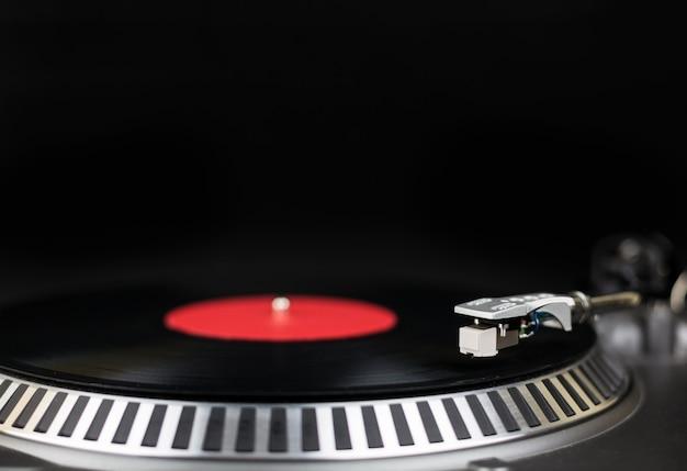 턴테이블 클로즈업 샷. 나이트 클럽에서 콘서트를위한 아날로그 무대 오디오 장비. 비닐 레코드에서 믹스 음악 트랙을 재생합니다. 턴테이블 니들 카트리지가 비닐 디스크를 긁습니다. 축제를위한 dj 설정