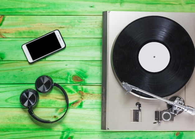 Turntable vinyl record player; headphone and cellphone on green wooden backdrop