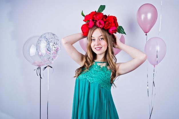 Счастливая девушка в зеленых платье и венке turqoise при покрашенные воздушные шары изолированные на белизне. празднование дня рождения тема.