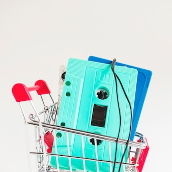 Turquoise and blue cassette tapes in shopping trolley against white backdrop