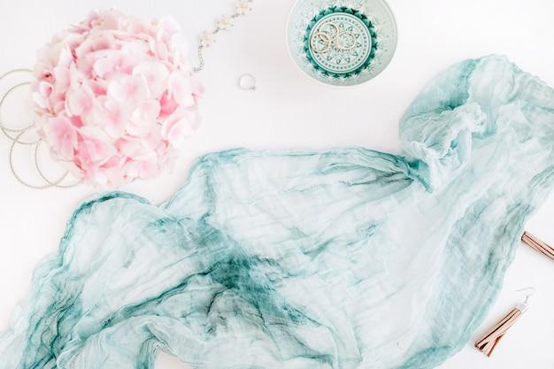 ターコイズブルーの毛布、カラフルなパステルアジサイの花の花束、白い表面の女性のファッションアクセサリー
