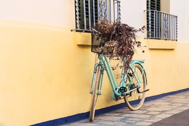 Бирюзово-синий велосипед, прислоненный к желтой стене в ситжесе