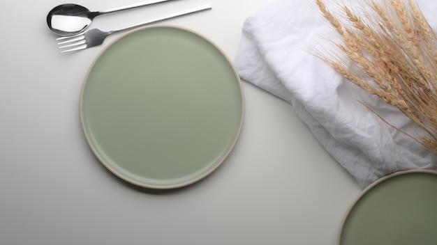 ターコイズブルーのセラミックプレート、銀器、ナプキン、黄金の小麦が白いダイニングテーブルに飾られました。