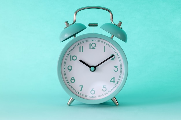 Turquoise classic alarm clock at ten in morning on mint background. start of the working day concept
