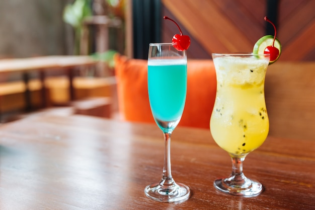 Turquoise color cocktail and passion fruit cocktail served with fresh cherry.